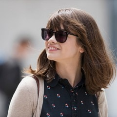 A woman with smooth hair, smiling and wearing sunglasses.