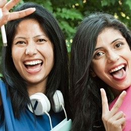Two women laughing and making two-fingered peace gesture at the camera. One of the girls is wearing large headphones and holding a school notebook.
