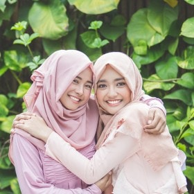 Two women wearing hijabs, hugging each other